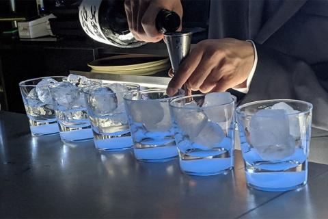 蓄光式のロックグラスで日本酒を提供するのも獺祭バーの特徴。薄暗い店内は、旭酒造の酒蔵がある、人工的な明かりがほとんどない夜を表現しているとのこと