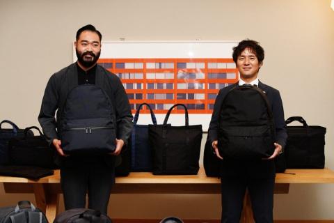 「モノリス」のデイパックを手に持つセイバンの泉貴章社長(右)と、ブランド開発を担当した中室太輔ディレクター(左)