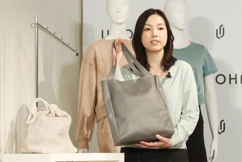 環境に配慮したレザー素材使用のトートバッグを手にするウィメンズクリエイティブスタジオ・マネージャーの三浦亜友氏