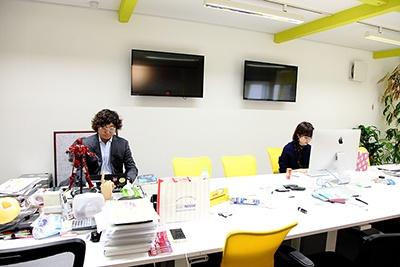 早朝のC Channel社内。とてもシンプルで黄色の椅子や柱が印象的。席は特に決まっていないという