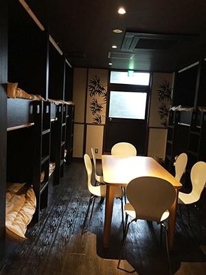 二段ベッドのドミトリー(相部屋/1ベッド2900円~)にはロッカーや共用のテーブルがある