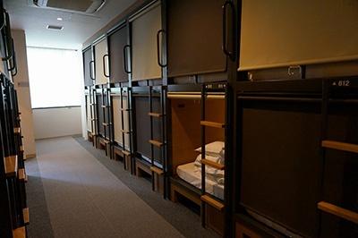 「グリッズ日本橋イースト」の「デザイナーズPOD」(2段ベッド)タイプの部屋(1泊3300円)。二段ベッドはきしみ音がないように特注スチール、密閉性の高いロールカーテンを使用し、鍵のかかる大型ロッカーもある