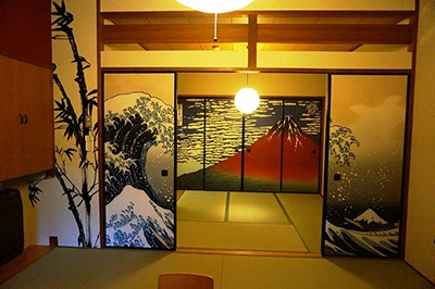 襖絵に北斎の富岳三十六景などが描かれた和室(個室)は4名部屋1室1万1700円~、6人部屋1室2万4500円~。手前の襖絵が富士山遠景で、開けると奥には大きな赤富士が見える趣向