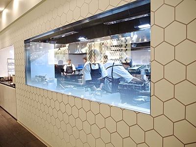 従来店でも厨房が見られるのは同じだが、中華料理の醍醐味である中華鍋を使った調理をガラス越しに見られる