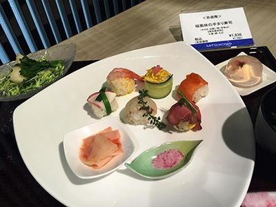 3月16日から4月5日まで提供されるセットメニューのひとつ「桜風味の手まり寿司(サラダ、吸い物、甘味付き)」(税込み1836円)。酢飯は具材に合わせて梅酢入り、大葉と白ゴマ入り、錦糸卵入りを使い分けている。箸休めには柑橘ドレッシングとハチミツのマリネ液に漬け込んだジャガイモの漬け物、ハマグリと菜の花の吸い物、カブと菜の花のスプラウトサラダ付き。デザートは桜ゼリー