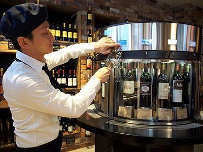 フードバル&ワインショップ「徳岡」。10万円以上の高級輸入ワインを1000円台で楽しめるというテイスティングコーナーは要チェック。2台のワインサーバーに用意された32種類のワイン を10mlから試飲できる。約300種類のインポートワインのほか、直輸入チーズと生ハムも販売
