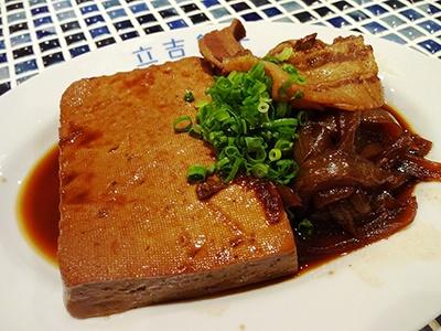 常連が必ず頼むという人気メニュー「豪快!肉豆腐」(590円)はタレを真っ黒になるまで染み込ませた豆腐。トロトロになるまで煮込んだタマネギ、豚肉、ネギを添えている