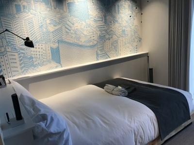 「スタンダードプラス」(26~35平米)はスタンダードルームにバルコニーやロフトの付いた客室。1室あたり3万5078円~。1~3人まで宿泊可能。壁の絵は渋谷の風景を描いたもの
