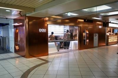 東武池袋駅構内にオープンした生どら焼き専門店「DOU」池袋店。営業時間は10~22時。通路に面したガラス窓は右から左に向かって流れ作業でドウを完成させる様子が眺められる。店舗デザインは、古くから和菓子の調理器具として使われてきた銅をモチーフにしている