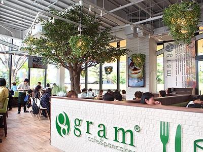 大阪発祥のパンケーキ専門店「グラム」の店内には大きな樹木が植えられ、ナチュラルな雰囲気。数量、時間限定販売のプレミアムパンケーキがおすすめ