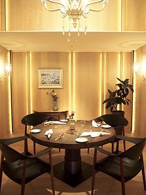 窓のないダイニングルームは高い天井に豪華なシャンデリアが飾られている