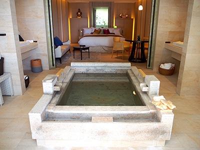 部屋の中央に占有の広い温泉風呂が配置された別棟のダブルルーム。風呂場には床暖房が入っていて冬場でも冷たくない。風呂の湿気が入ってこないよう空調を工夫している