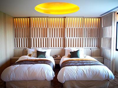 本棟の客室は全室ツイン。和と洋を融合したインテリアが印象的。夜になると、木製のルーバー付き引き戸から漏れる柔らかな照明が雰囲気を盛り上げる。天井の凹みは満月のよう