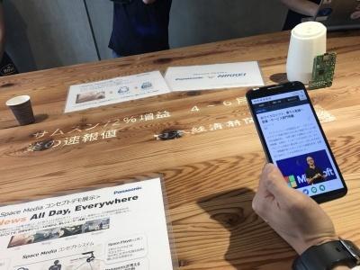 どこでも自然な形で欲しいニュースが読めるサービスのコンセプトモデル「Space Media」。スポットライトのようなプロジェクター「Space Player」と、スマートフォンをかざすだけで情報を読み取ることができるサービス「LinkRay」、状況に合わせて最適なニュースや情報を提供する「Media Engine」を組み合わせた、日本経済新聞とパナソニック有志グループによる実証実験