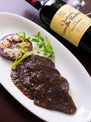 「和牛の赤ワイン煮込み 薄切り仕立てのグラタン 蓮根ドフィノワーズ」(1800円)。真空調理でもっちり軟らかく仕上げた牛ホホ肉をピノ・ノワールワインでマリネし、付け合わせにホワイトソースを絡めたレンコンを添えている。赤ワインによく合う