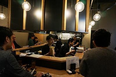 立ち鉄板「鉄板焼 芯 立ち呑みや」。16年間恵比寿で営業している鉄板焼き店が分店を初出店。おすすめは、自家製マヨネーズで味付けした「有頭エビとブロッコリーのマヨネーズ焼き」(580円)