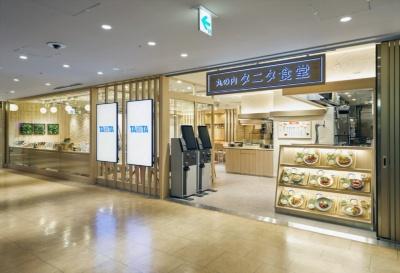 「丸の内タニタ食堂」(東京都千代田区丸の内3-1-1 丸ノ内国際ビルヂング地下1階)。営業時間はランチタイム11~15時、カフェタイム15時~17時半、ディナータイム17時半~22時。席数64。店内もリニューアルし、以前よりリラックス感のある内装に