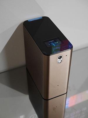 上面壁側の青白く光る棒状の部分から赤外線を出す。手前の四角い部分はプロジェクターと赤外線カメラが内蔵されている。前面の丸い黒い部分がカメラ
