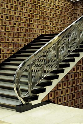 新有楽町ビル(1966年竣工)エントランスの階段ホール。民芸調の陶板タイルの壁面と、モダンなステンレス鏡面仕上げの手すりが融合した、圧倒されるほど美しいデザインだ