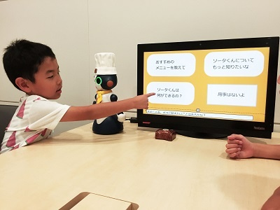 レストラン「ココス」での実証実験のデモ。タッチパネルを介してロボットが接客する(写真提供/ゼンショーホールディングス)