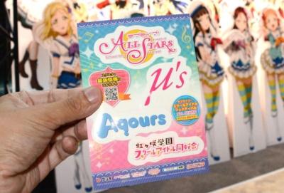 配布しているステッカー。『ラブライブ!』のμ's(ミューズ)や『ラブライブ!サンシャイン!!』のAqours(アクア)といったスクールアイドルのロゴが印刷されている。写真はビジネスデイに頂いた物