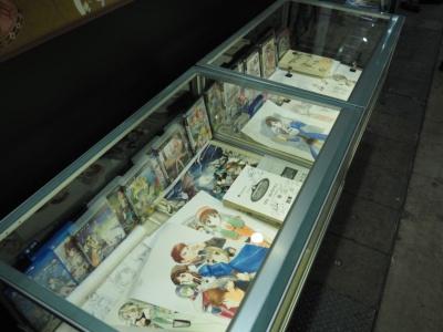 試遊台の右隣には、『アトリエ』シリーズの歴史をまとめたコーナーが。歴代のタイトルを年表にまとめたパネルや、過去作品のパッケージなどが収められたガラスケースが。直筆のキャラクター設定画や、アフレコ台本など、貴重なアイテムが見られるのだ