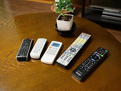 自宅リビングにあるテーブルの現状。右からテレビ、有線放送のセットトップボックス、エアコン、ミニコンポ、ブルーレイプレイヤーと5つのリモコンが並ぶ