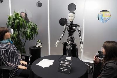 NTTの展示の目玉は、大阪大学の石黒浩教授がプロデュースするロボットと人間の自律的な会話のデモ。写真の中央だけでなく左もロボットで、右の人間と合わせて3人で自律的な会話を行っていた