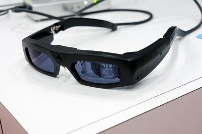 一般的なメガネとほぼ同じサイズを実現しているレーザアイウェア。向かって右側の目の部分に超小型プロジェクターを装備しており、網膜に直接投影する