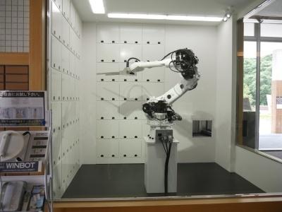 クロークサービスでは、ロボットアームが荷物を出し入れする