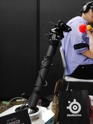 「テレイグジスタンス」は、自在に動くアーム型のロボットに取り付けられたカメラの映像をVRゴーグルで見る装置で、自分の動きに合わせてロボットも動く