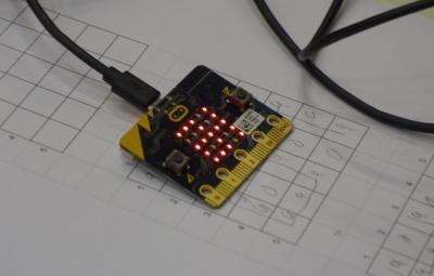 ひらがなの「み」を表現しているのだけど、わかるかな? マイクロビットの下にあるのは、LEDにどんな記号や文字を表するかを考えるための「5×5マス」の下書き用メモ