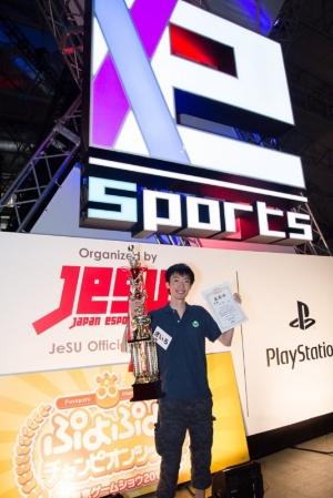 巨大なトロフィーと賞状を手にする優勝したざいろ選手。賞金100万円のほか、副賞として「PS4 Pro」も獲得した。