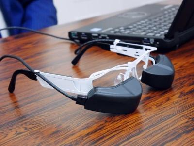 b.g.は、メガネのレンズの外側にディスプレーが付いている。左右それぞれの目でディスプレーを見ることで、見やすさを改善した