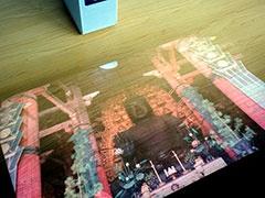 木目のテーブルに投影したイメージ。村澤氏は「木目のある壁紙でも、人間の目は状況に合わせて適応するのでそれなりに見える。人間の目って本当にすごい」と笑って話す