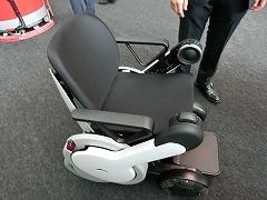 WHILLの「WHILL NEXT」は、人が座って乗る車椅子型のパーソナルモビリティー。遠隔操作で降りた場所から自動回収もできるという