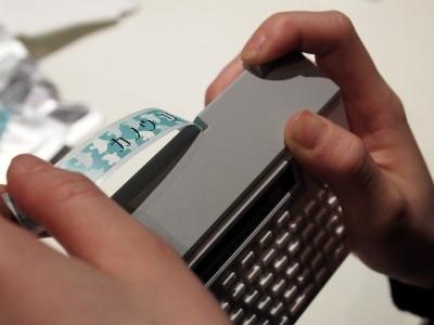このように印字されたテープが出てくるので、煙突形のカットボタンを押してカットする