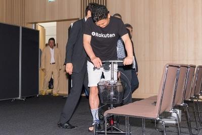 三木谷会長兼社長は足に包帯を巻いて、キックボードのような歩行を補助する器具に乗って登場
