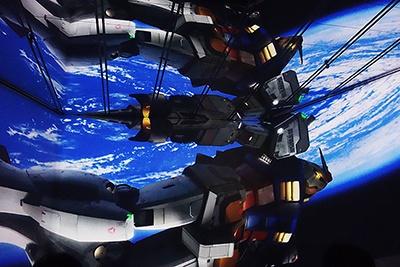 スペシャルシアターの映像。写真では分かりづらいかもしれないが、下のスクリーンの映像が天井の鏡にも映っているのが確認できるだろうか。VRや3Dとは違った映像体験が楽しめる<br>(C)創通・サンライズ/(C)創通・サンライズ・MBS/(C)創通・サンライズ・テレビ東京