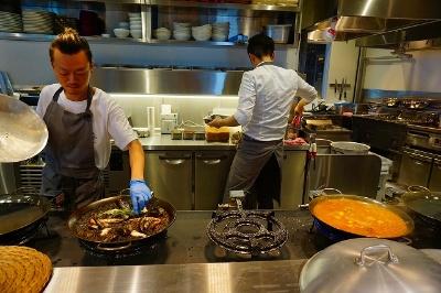 トランジットジェネラルオフィスがプロデュースするスペイン料理「XIRINGUITO Escribà(チリンギート エスクリバ)」。入り口をくぐってすぐ右手にあるオープンキッチンでパエリアを作っている様子が見られる