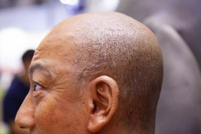 """細かなシワ、毛穴のブツブツまで写し取り、彩色で見た目のリアリティーに限りなく近づけるパーフェクションスーパーリアルマネキン。髪の毛は1本1本""""筆で描いた毛""""だが、巧みな筆使いにだまされて遠目にはそれらしく見える"""