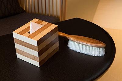 小物にも哲学が宿る。継ぎ目がなめらかな竹のティッシュボックスと、日本橋大伝馬町の老舗「江戸屋」による豚毛の洋服ブラシ