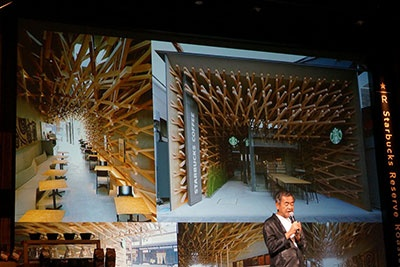 設計を担当する建築家の隈研吾氏。(背景は同氏が設計した「スターバックス コーヒー 太宰府天満宮表参道店」)。入口から店内にかけて伝統的な木組み構造を用いており、店舗の奥庭には太宰府天満宮のシンボルでもある梅の木が植えられている
