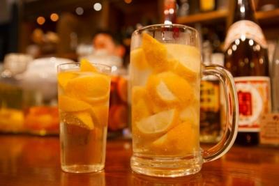 「酒場エビス」(京都市中京区)で人気の「名物レモンサワー」は「進化系レモンサワー」のひとつ。広島県産レモンをグラス1杯につき1個(ジョッキは2個)使い、蜂蜜とレモンを合わせて漬け込んだ甲類焼酎をベースに、強炭酸で割っている(写真:宝ホールディングス)