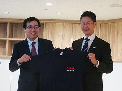 オープニングセレモニーではカルビーの伊藤秀二社長兼COO(左)が湯崎英彦広島県知事(右)にラボメンバーの証しとしてTシャツを贈呈
