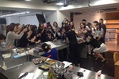 スマホカメラで熱心に撮影する料理教室の参加者たち